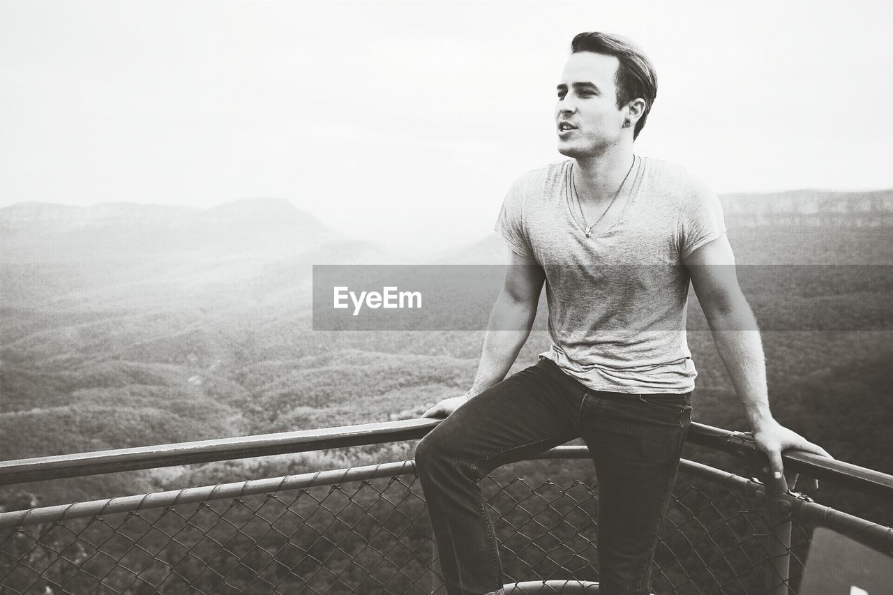 Young man sitting on railing against mountains