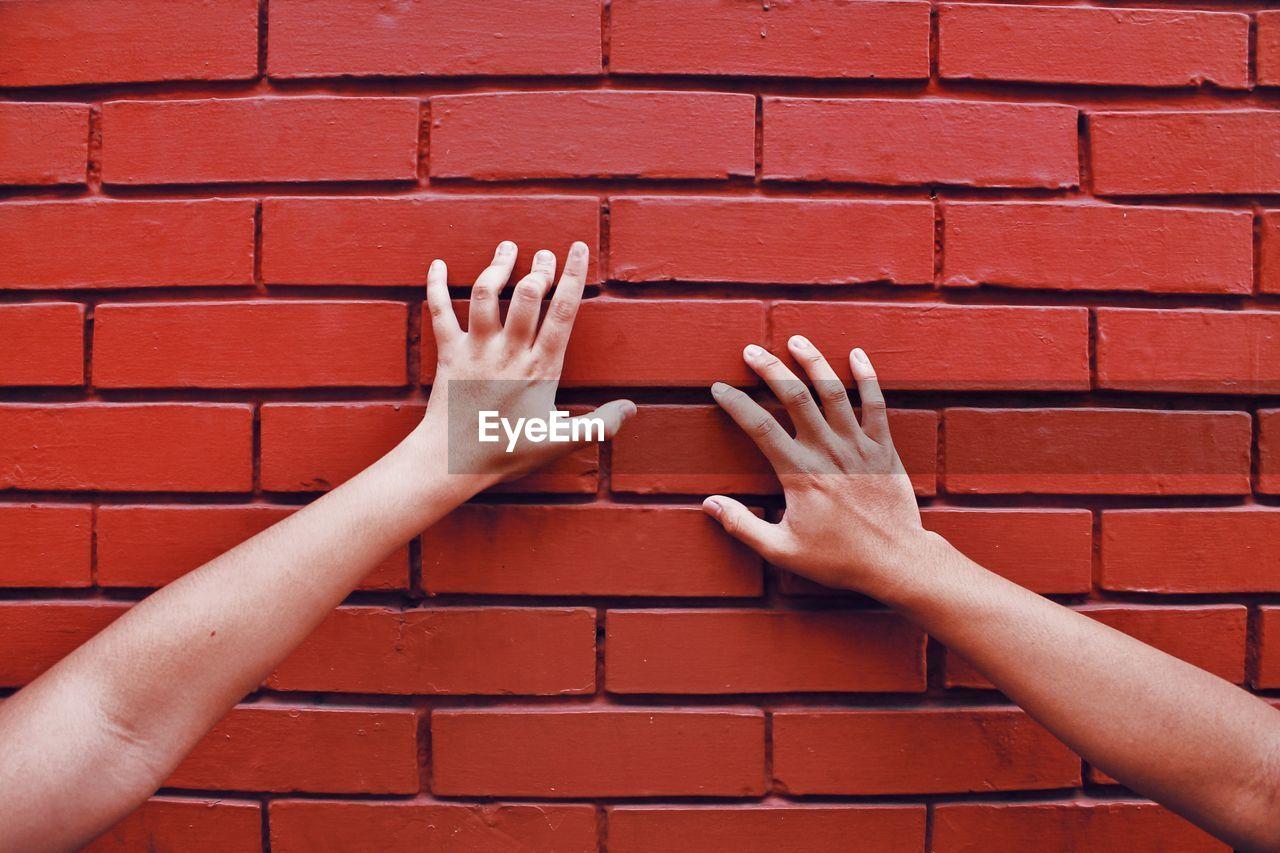 Cropped image of women touching brick wall
