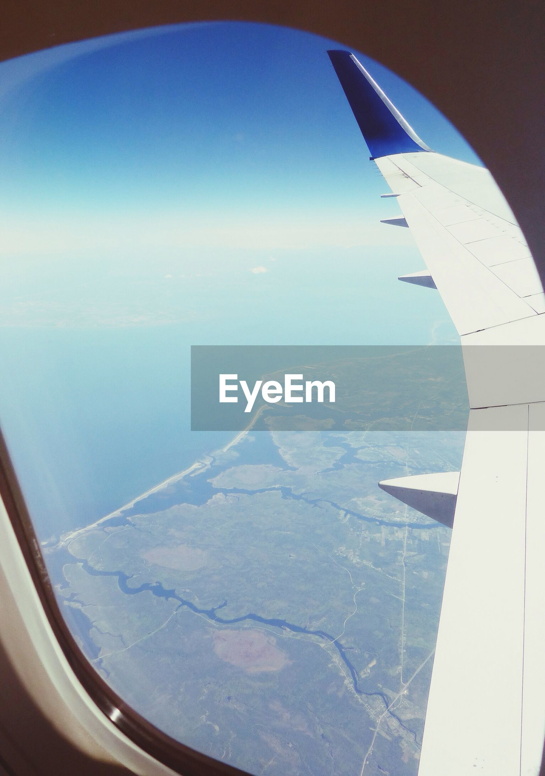 airplane, aircraft wing, air vehicle, flying, aerial view, transportation, part of, cropped, mode of transport, mid-air, sky, travel, scenics, blue, landscape, airplane wing, beauty in nature, journey, nature, window