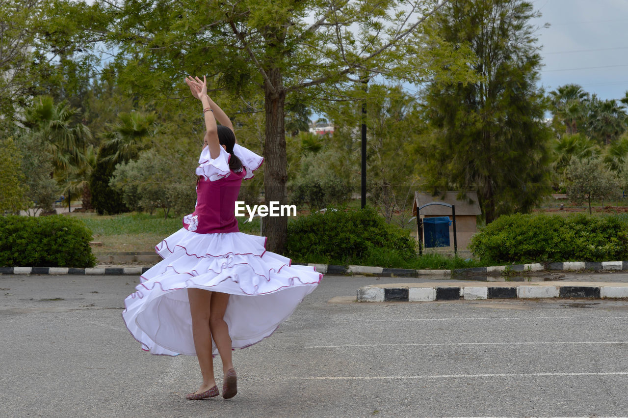 Rear view of girl dancing on street at park