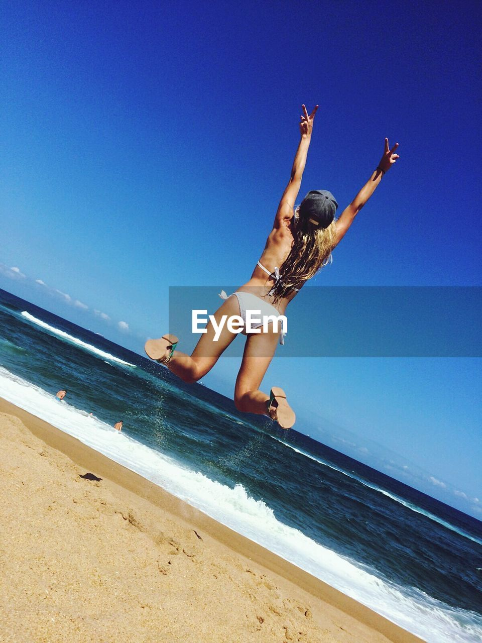 Rear View Of Young Woman Wearing Bikini Jumping At Beach