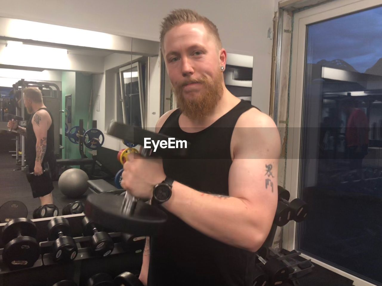 Portrait of man holding dumbbell at gym