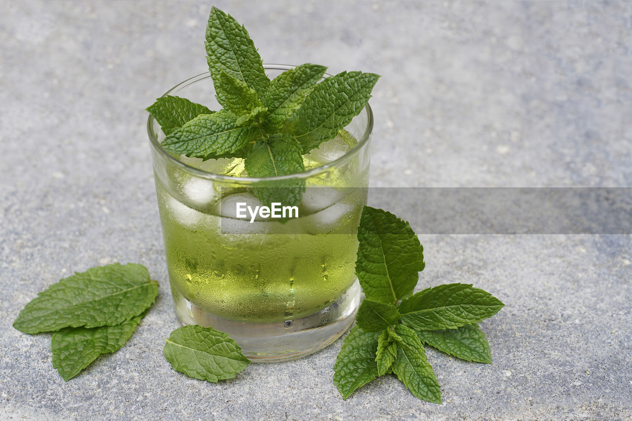 Green cool mint drink in front of concrete background