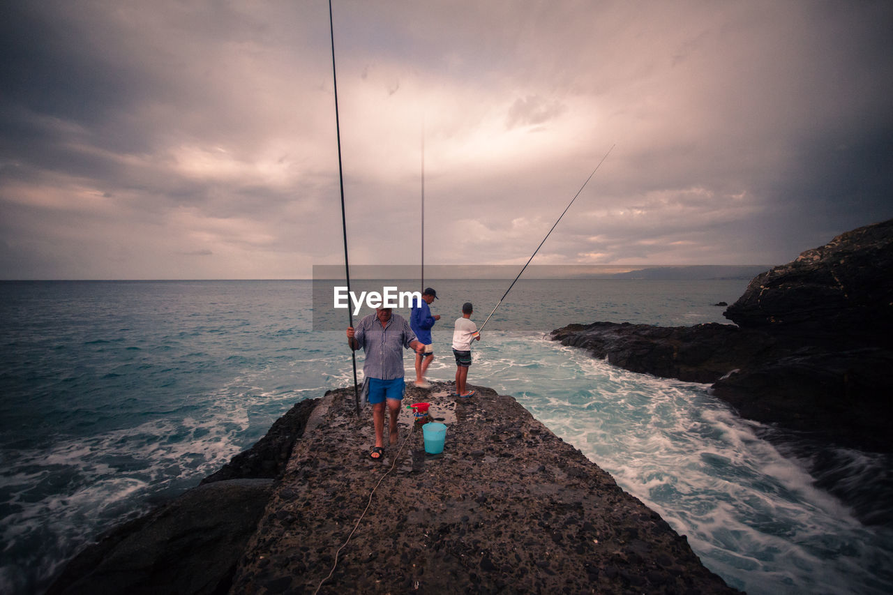 Men fishing while standing on rock in sea against cloudy sky
