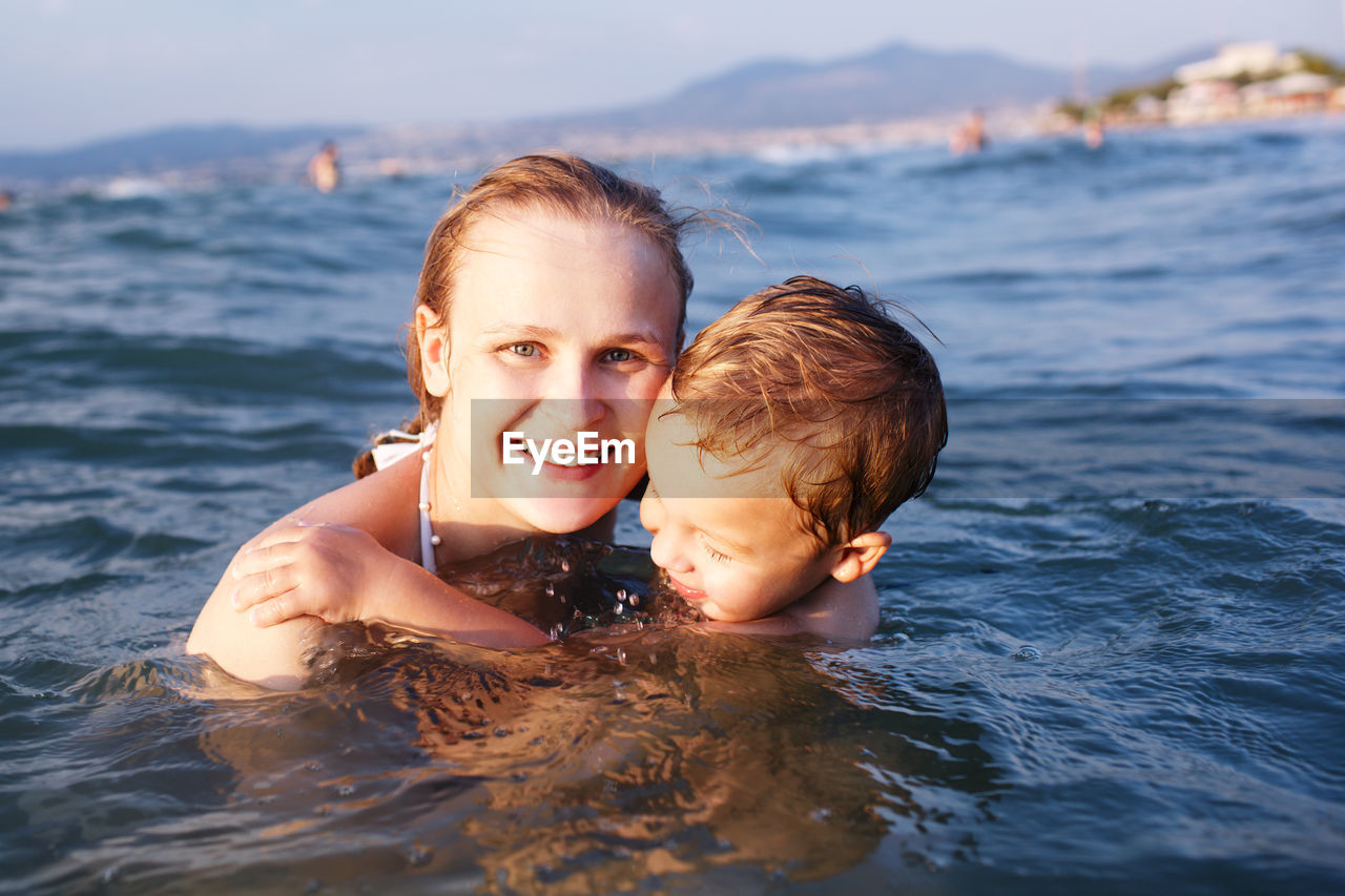 Portrait Of Happy Mother Swimming With Son In Sea