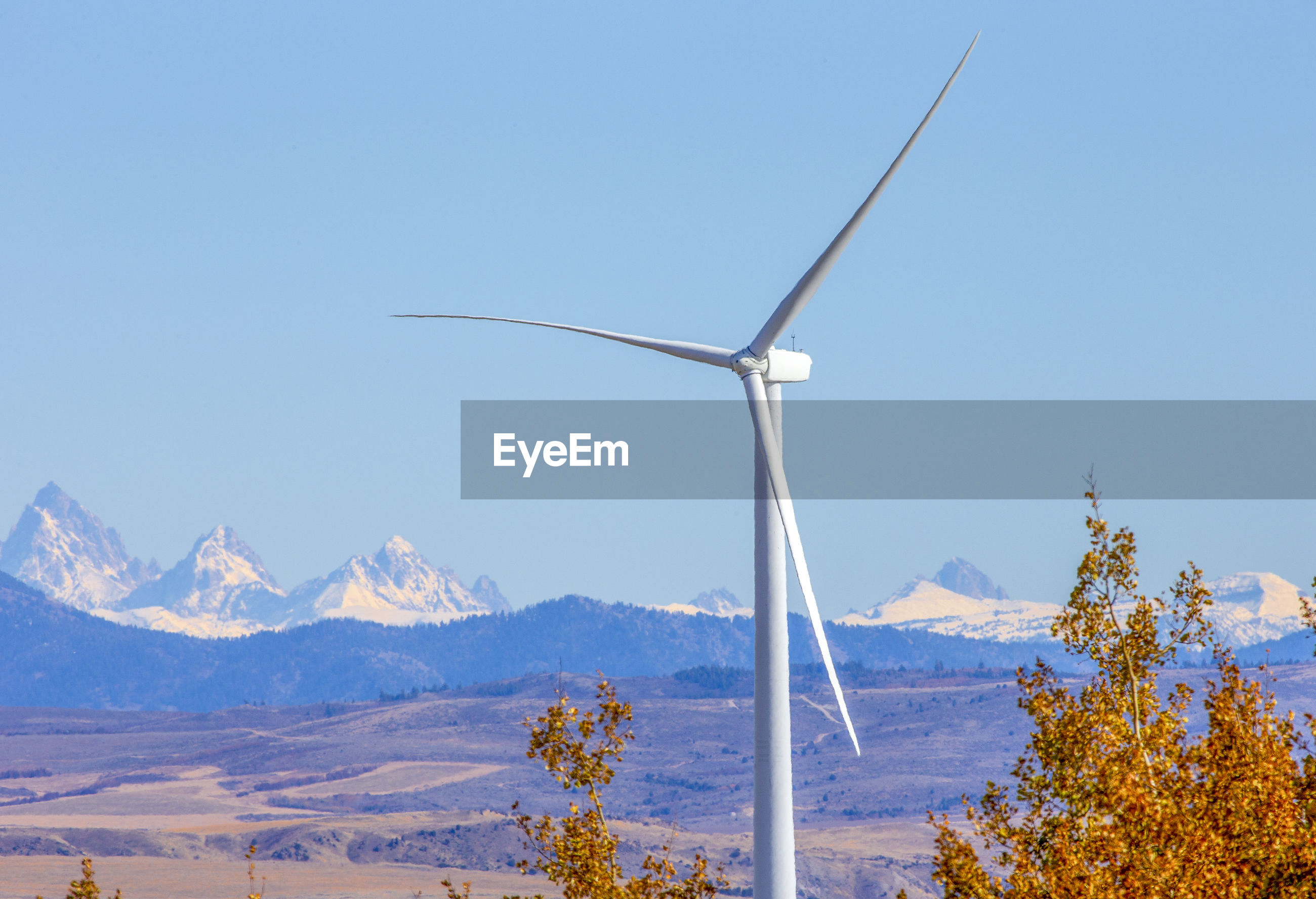 WIND TURBINES ON SNOWCAPPED MOUNTAIN AGAINST SKY