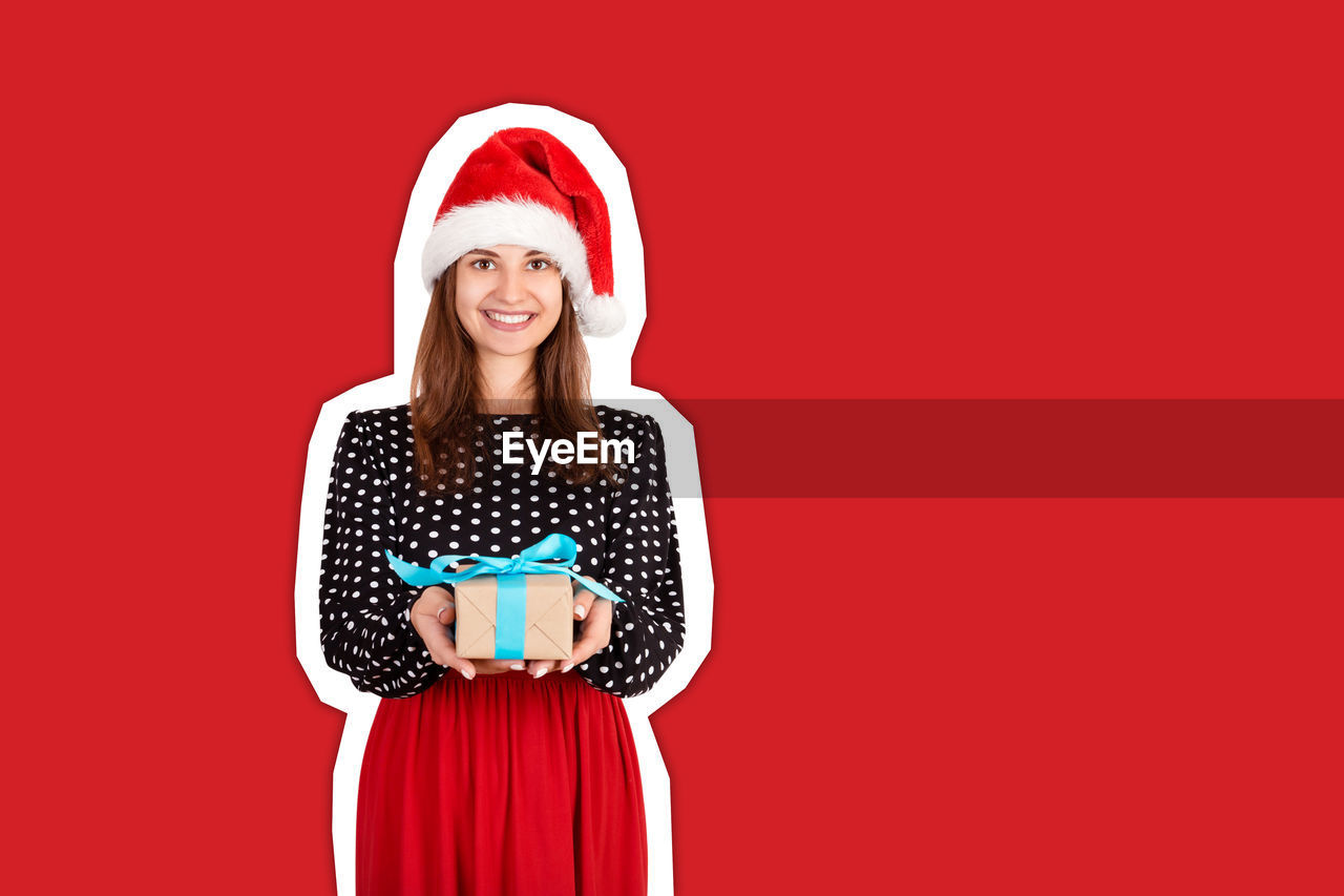 Portrait of smiling woman holding gift box against red background