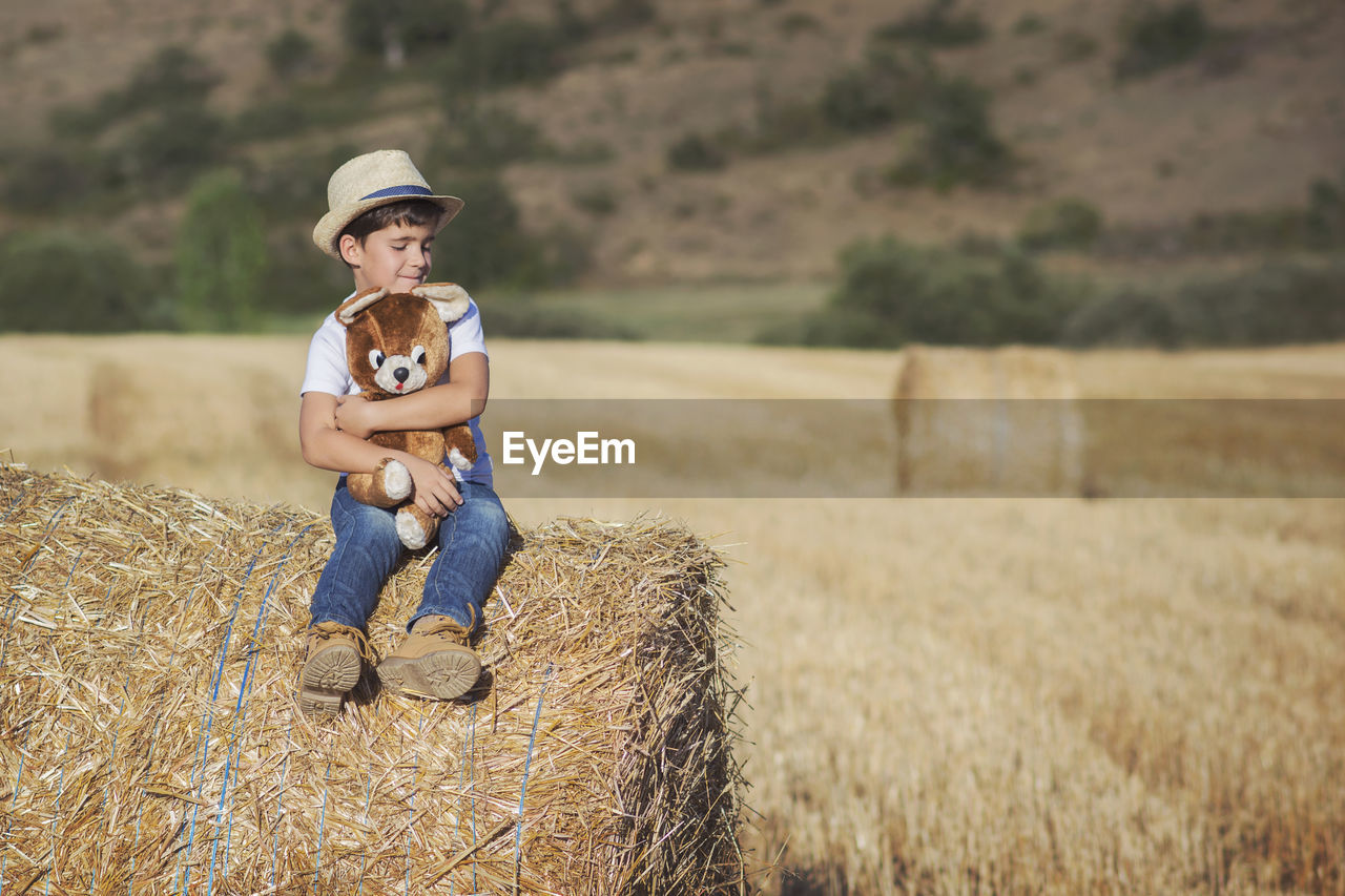 Full Length Of Boy With Toy Sitting On Hay Bale At Agricultural Field