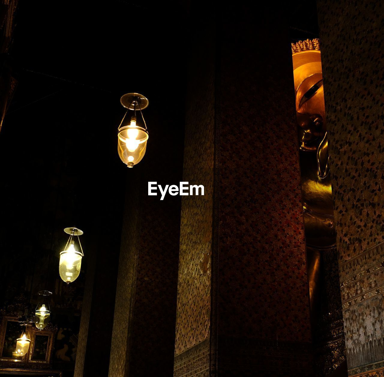 LOW ANGLE VIEW OF ILLUMINATED LIGHT BULB HANGING ON STREET