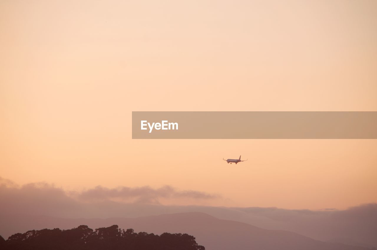 air vehicle, mode of transportation, airplane, flying, sky, transportation, sunset, orange color, beauty in nature, travel, mid-air, copy space, no people, nature, scenics - nature, on the move, motion, outdoors, silhouette, low angle view, aerospace industry