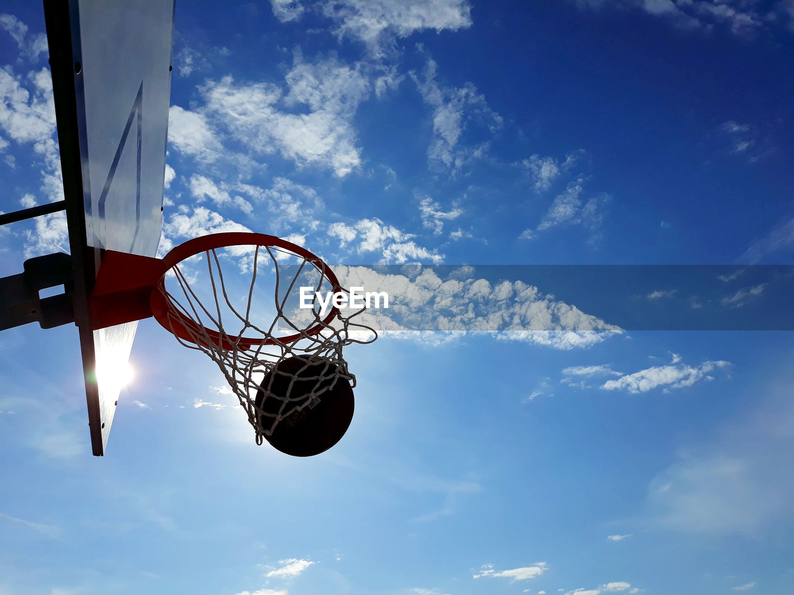 Low angle view of basketball in hoop against blue sky