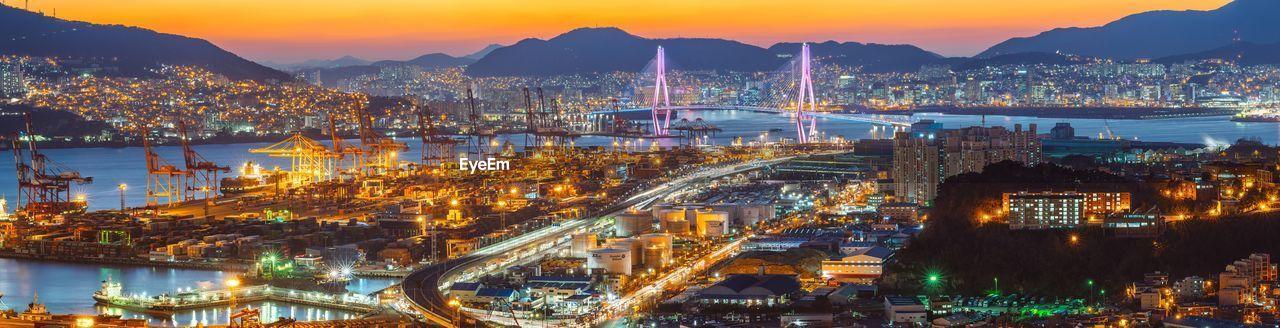 Panoramic View Of Illuminated Dock And Bridge In City