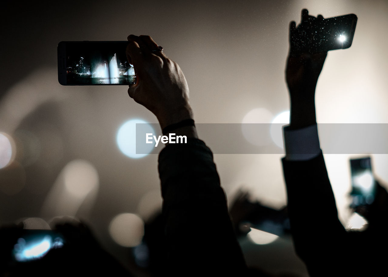 Cropped image of hands photographing through smart phones at concert