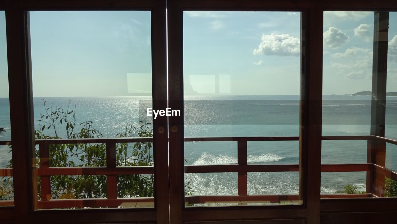 window, sea, railing, indoors, sky, scenics, water, no people, day, tranquil scene, nature, horizon over water, cloud - sky, luxury, beauty in nature, architecture, cityscape