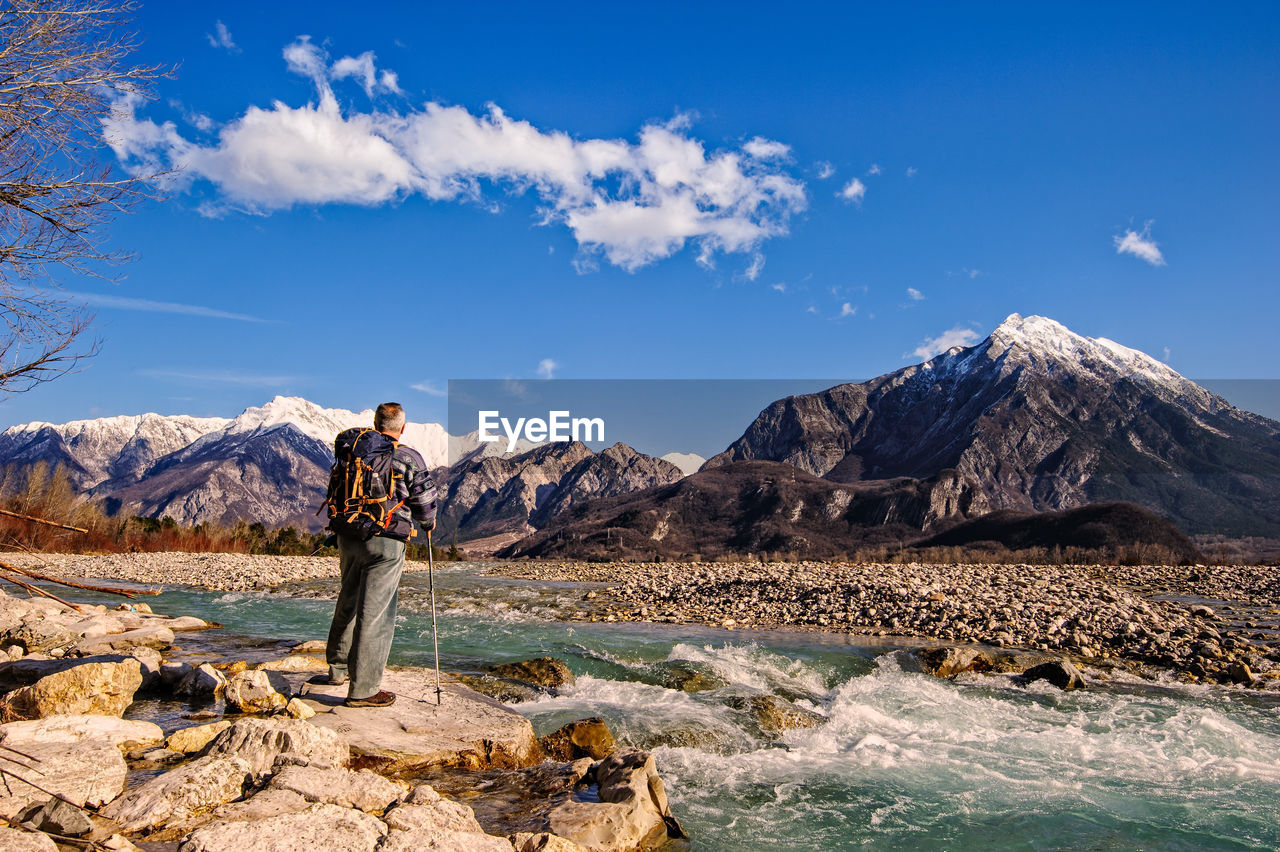Rear View Of Man Standing On Rock By River Against Sky