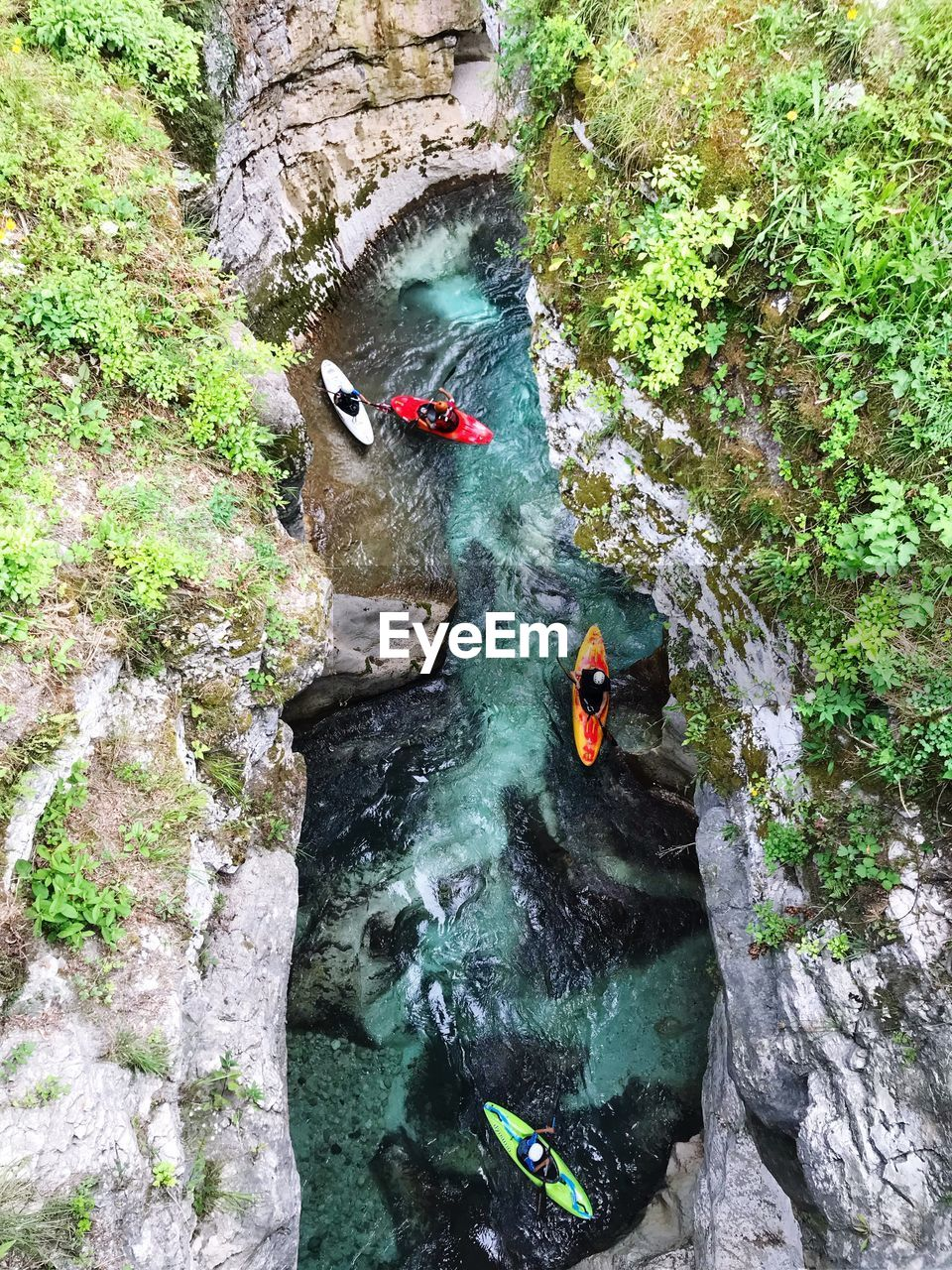 High Angle View Of People Kayaking On River Amidst Rock Formation