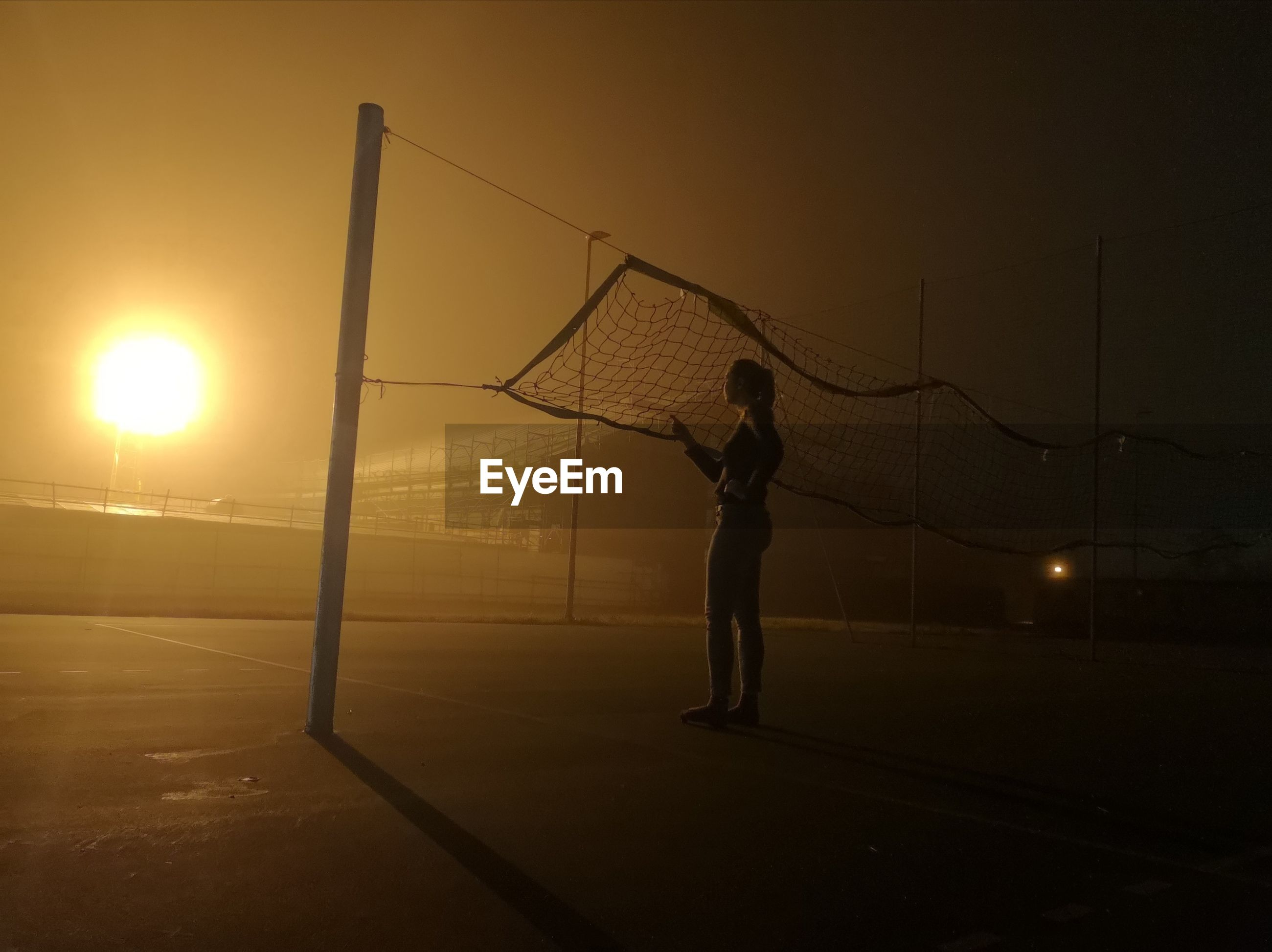 Full length of woman standing by volleyball net at night