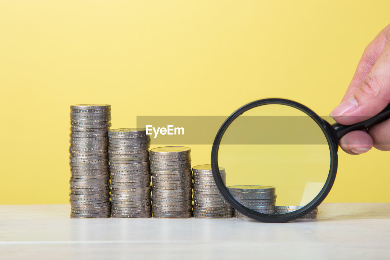 Cropped Hand Holding Magnifying Glass By Coins Against Yellow Background