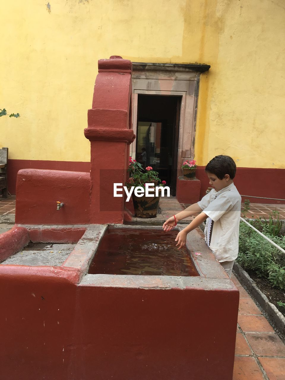 Side view of boy playing with water in trough at park
