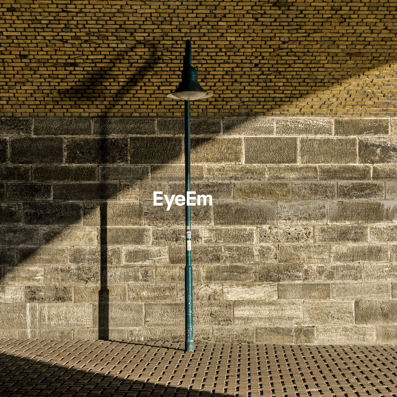 Green street light on sidewalk against brick wall
