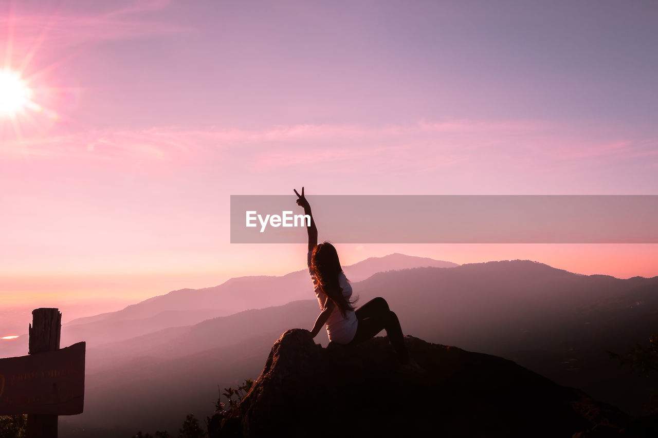 Woman Climbing On Mountain Against Sky During Sunset