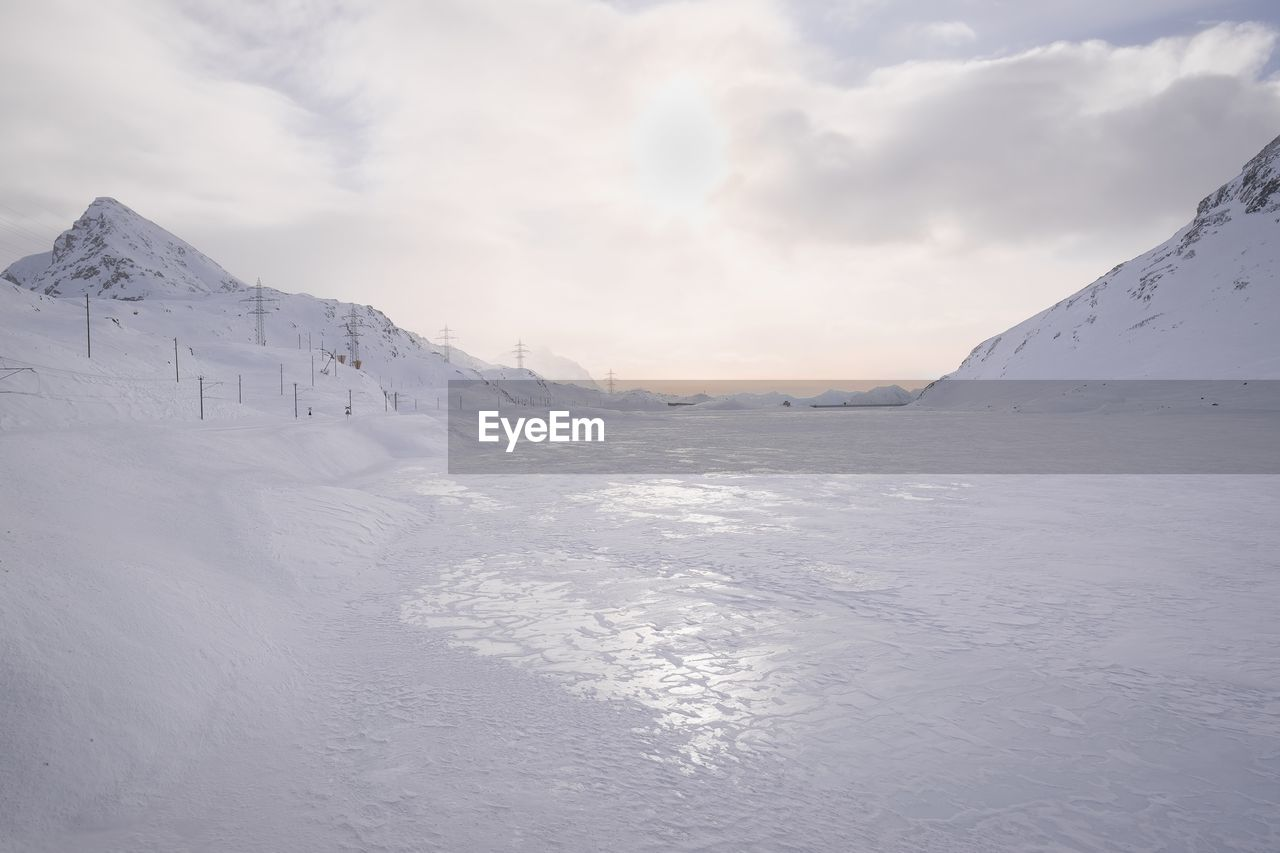 Scenic view of frozen lake against sky in winter