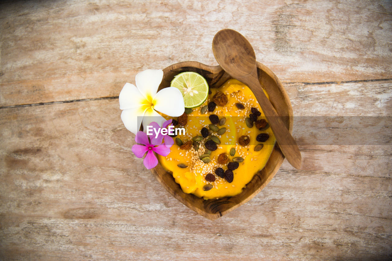 flower, petal, freshness, directly above, indoors, high angle view, table, no people, flower head, yellow, fragility, close-up, sweet food, nature, frangipani, beauty in nature, day, periwinkle
