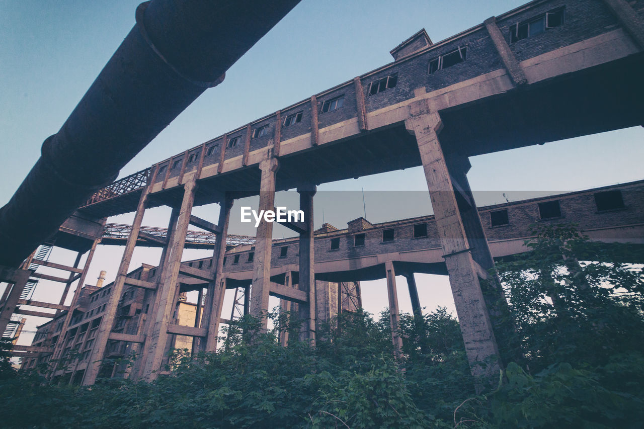LOW ANGLE VIEW OF ABANDONED BRIDGE AGAINST SKY