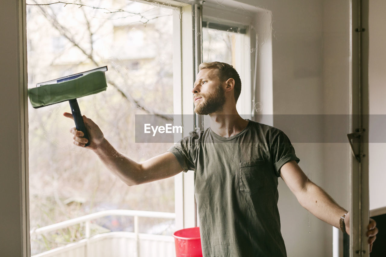 window, one person, real people, domestic life, lifestyles, casual clothing, standing, young adult, holding, indoors, home interior, young men, domestic room, day, waist up, front view, facial hair, looking, housework, preparation