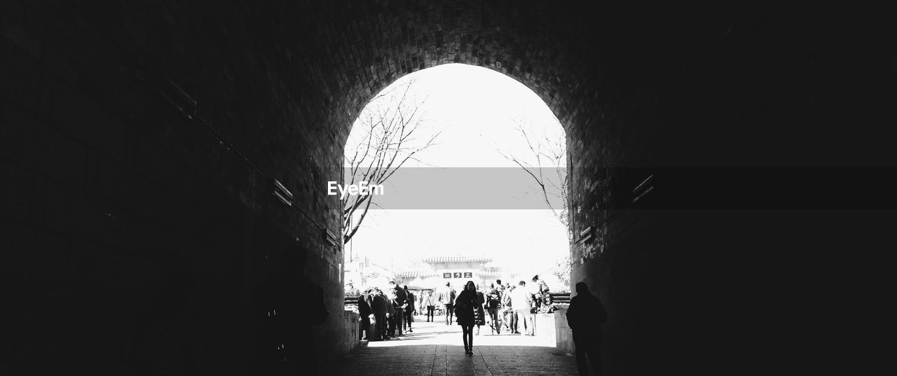 indoors, arch, real people, built structure, tunnel, architecture, light at the end of the tunnel, the way forward, day, women, men, large group of people, sky, people
