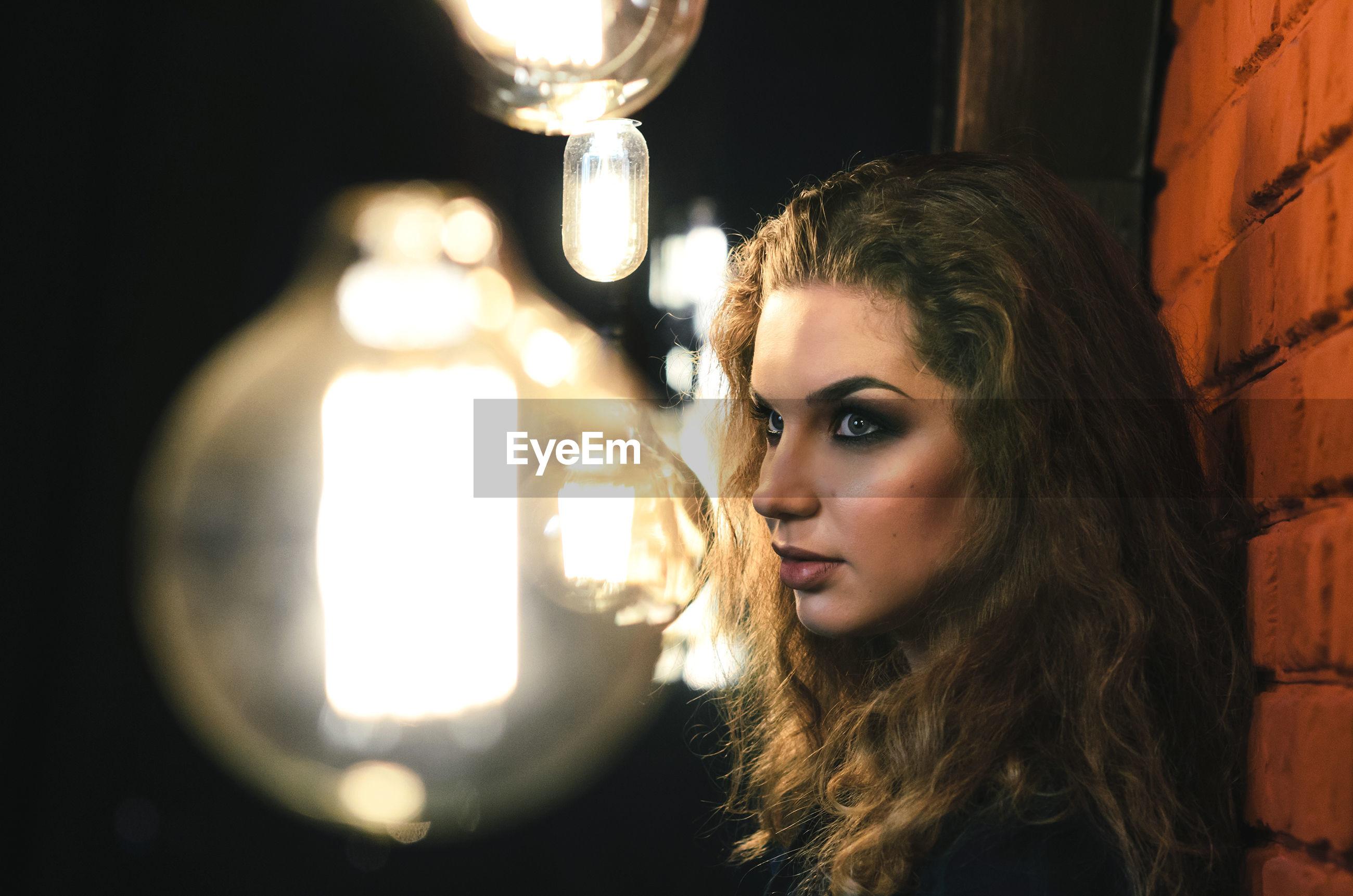 Woman by illuminated light bulb in darkroom