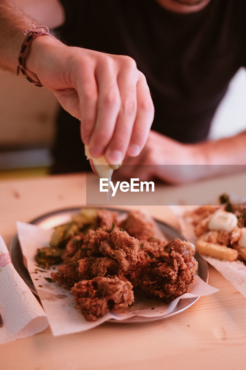 Close-up of hand squeezing lemon over fried chicken wings