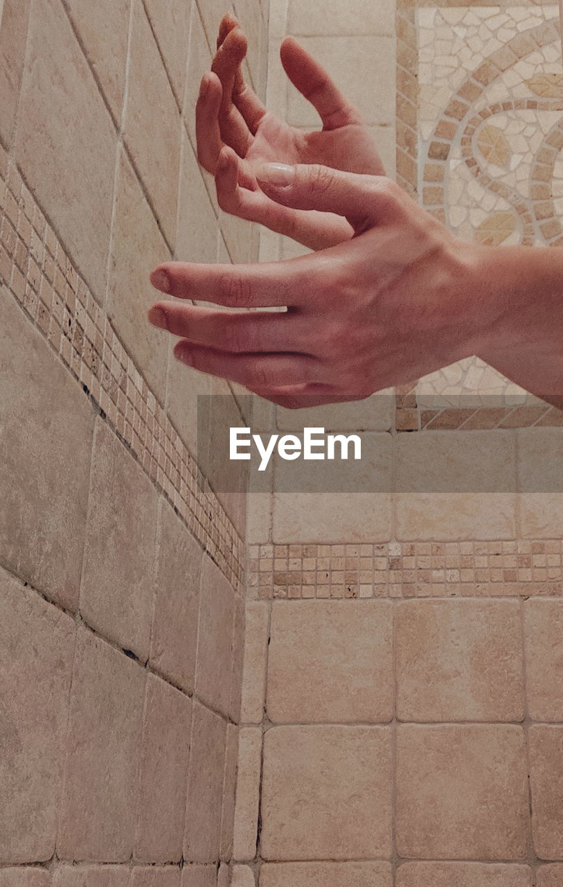Cropped hands against tiled wall
