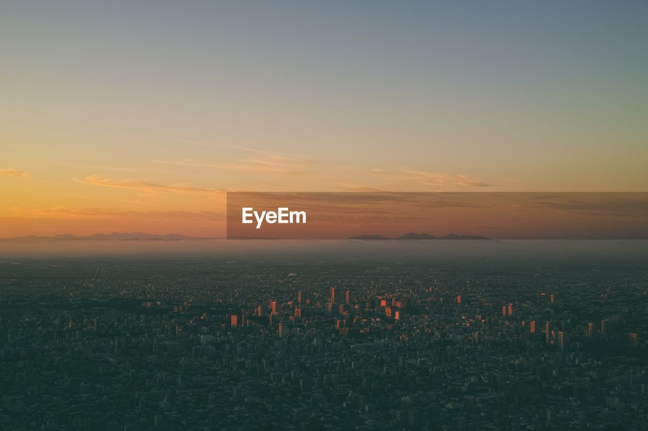 sky, sunset, orange color, beauty in nature, scenics - nature, nature, no people, building exterior, architecture, city, cityscape, copy space, cloud - sky, idyllic, built structure, landscape, outdoors, environment, horizon, tranquility, skyscraper