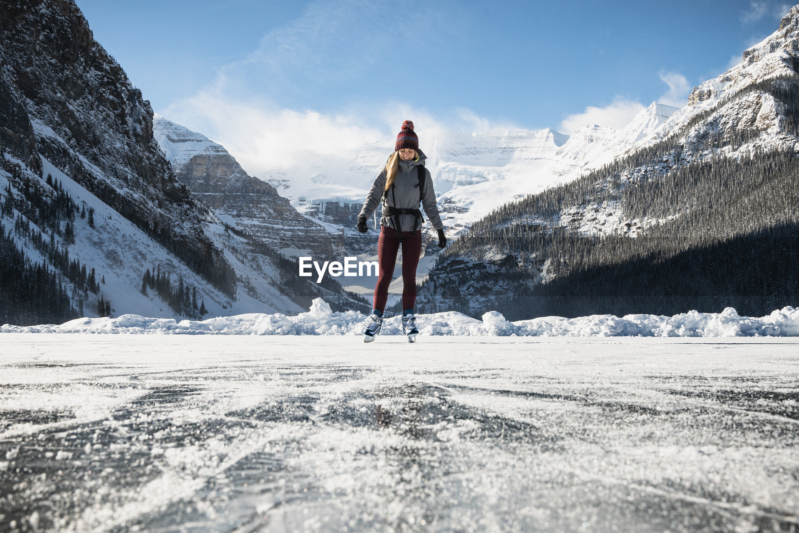 MAN STANDING ON SNOWCAPPED MOUNTAIN