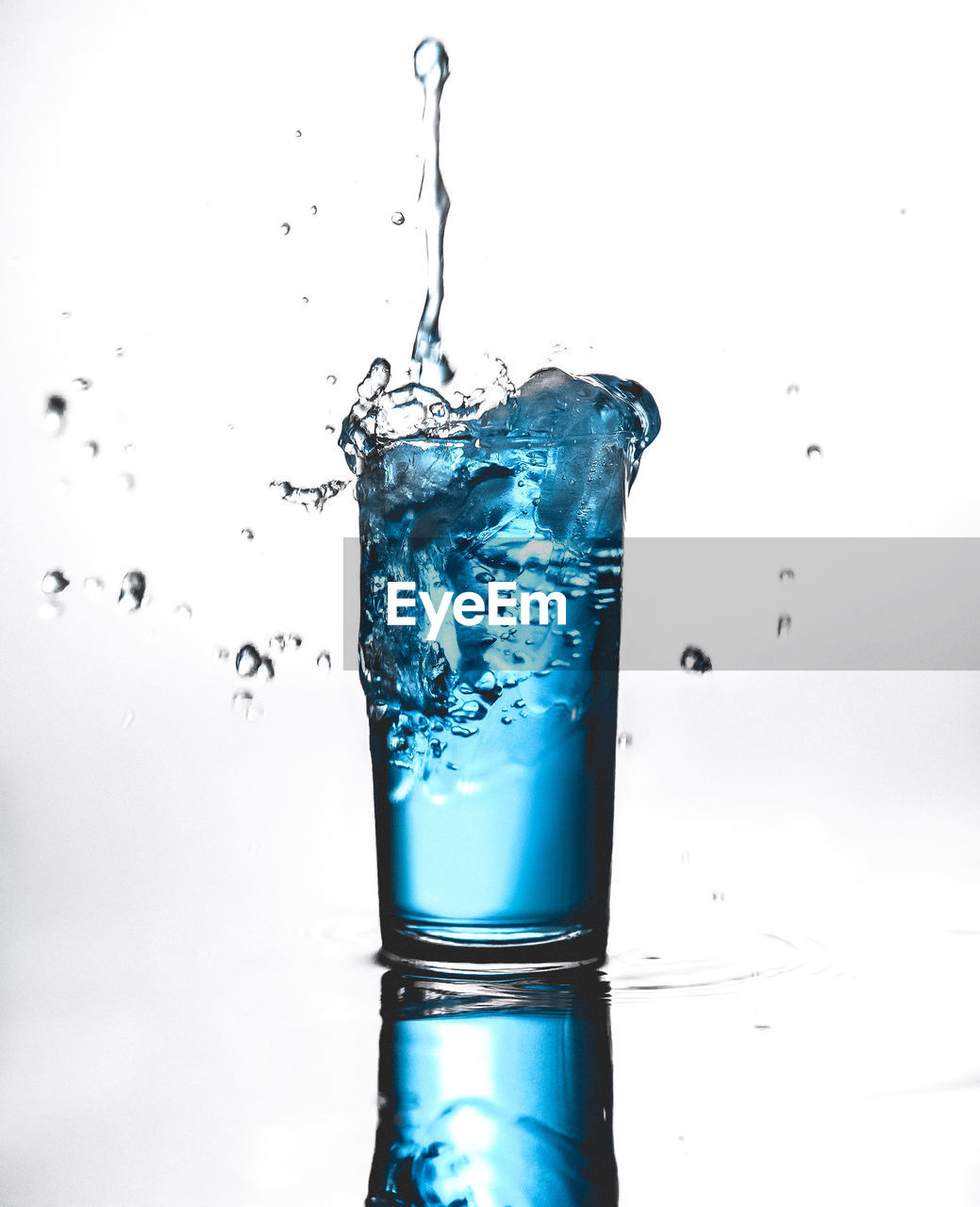studio shot, water, splashing, motion, drop, food and drink, glass, indoors, blue, freshness, drinking glass, white background, household equipment, refreshment, no people, close-up, nature, purity, drink, high-speed photography, clean