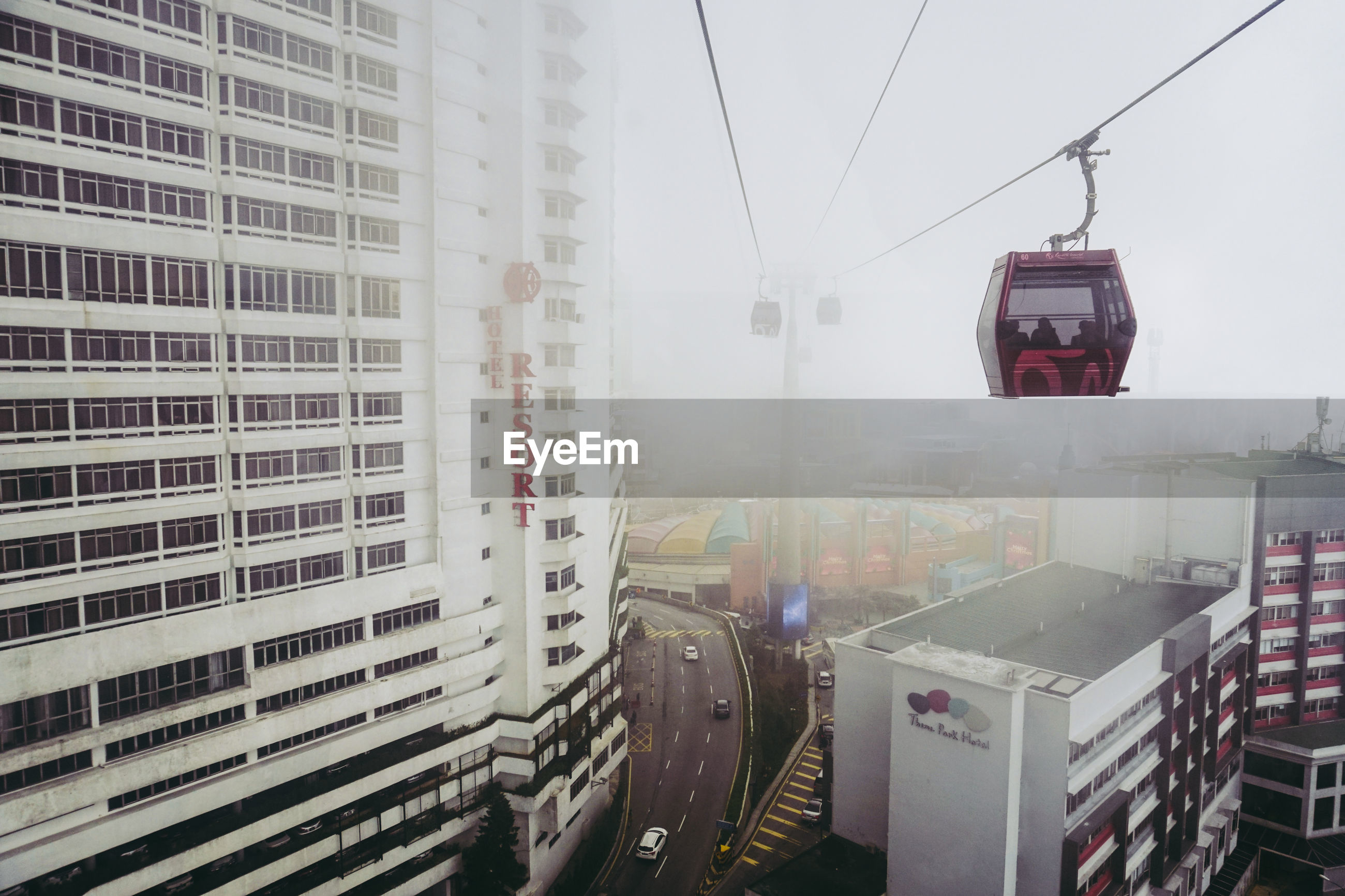 LOW ANGLE VIEW OF OVERHEAD CABLE CAR IN CITY