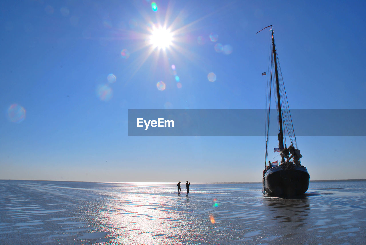 Silhouette men standing by boat moored on shore against sky during sunny day
