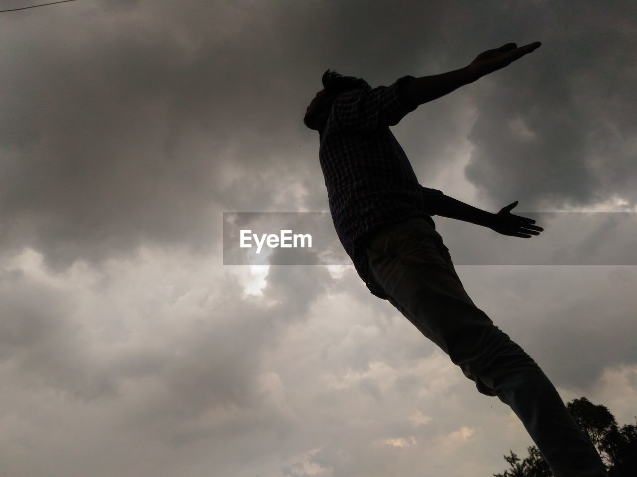 Low Angle View Of Man With Arms Outstretched Against Cloudy Sky