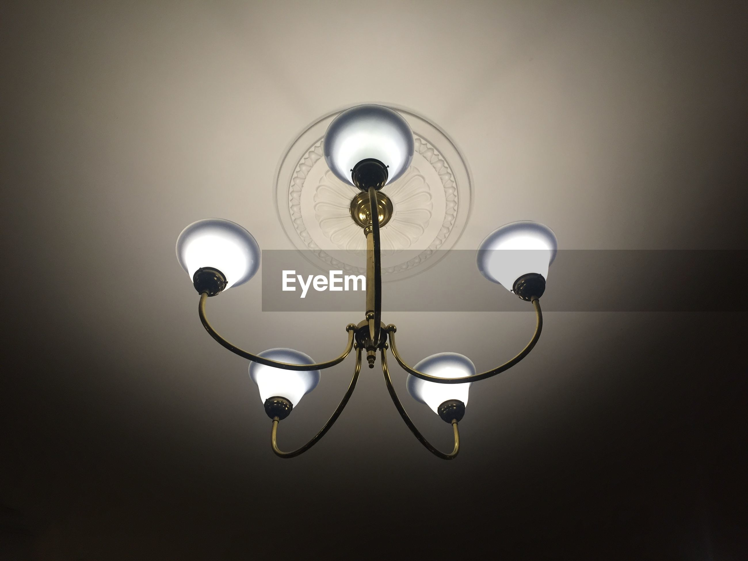 Low angle view of illuminated chandelier hanging from ceiling at home