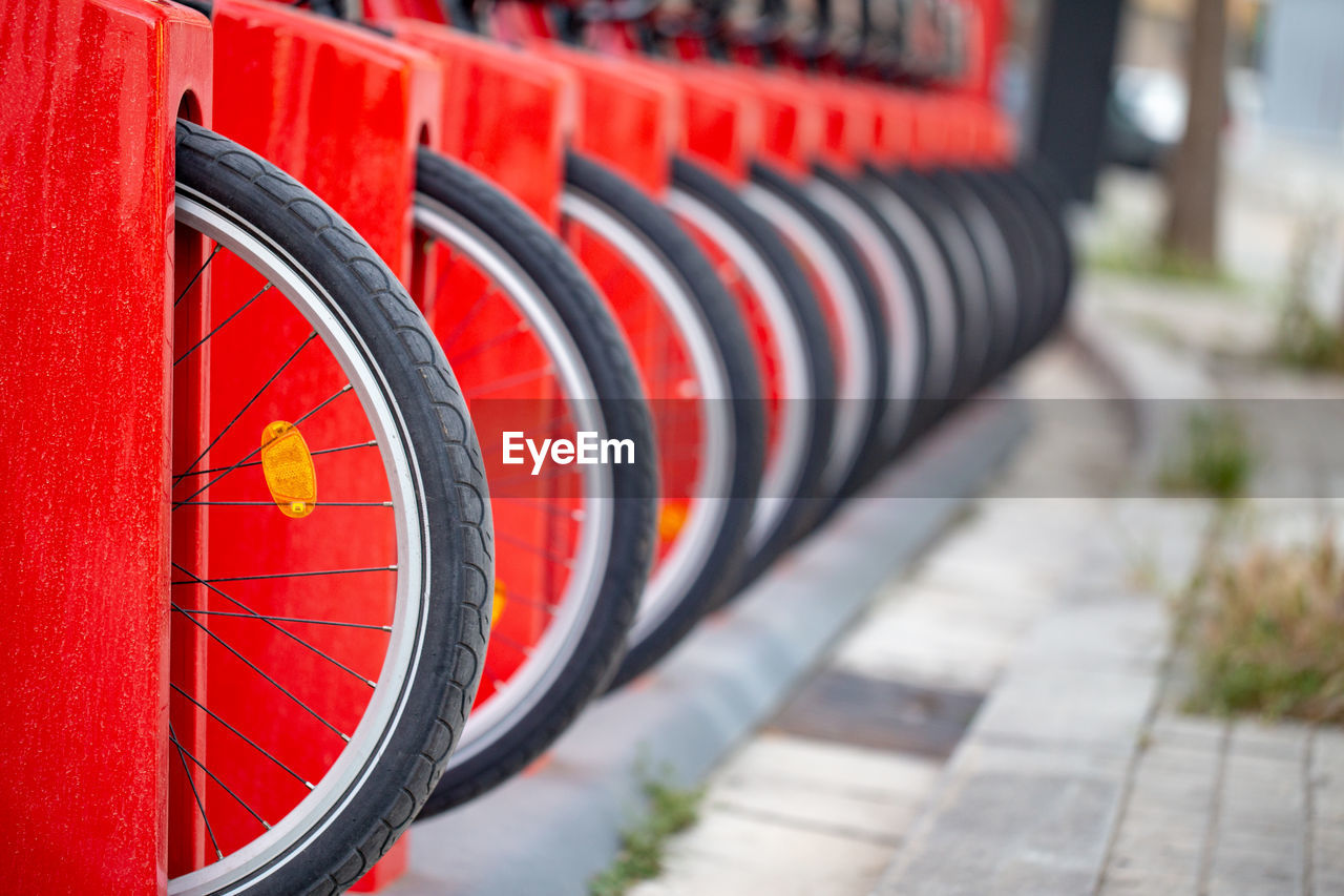 red, focus on foreground, selective focus, no people, in a row, day, metal, close-up, pattern, repetition, shape, outdoors, wheel, architecture, footpath, spiral, design, transportation, sunlight, orange color, tire