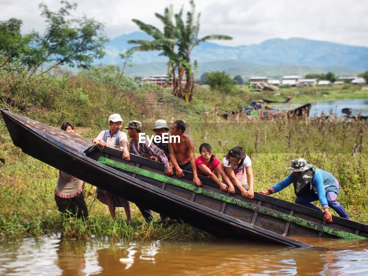 PEOPLE IN BOAT ON RIVER AGAINST SKY
