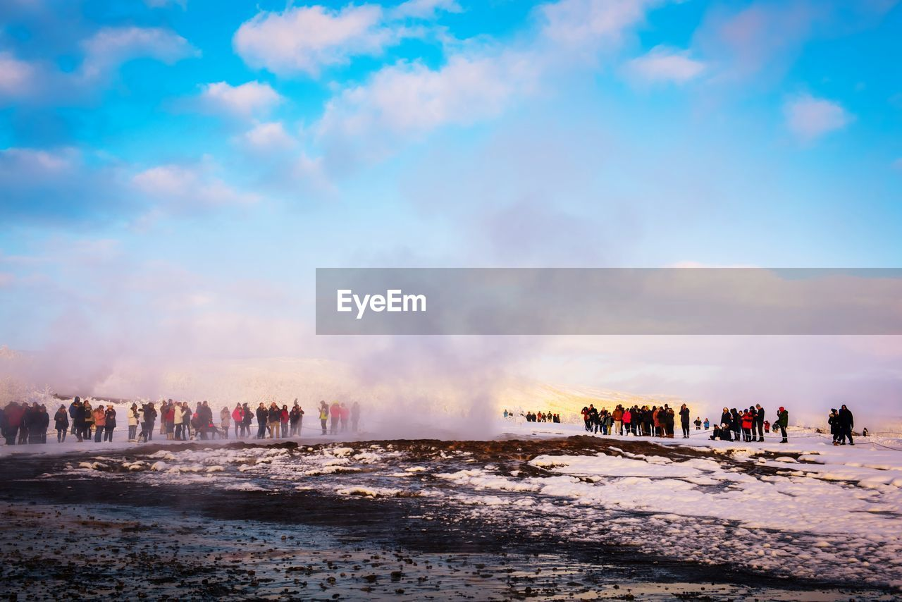 sky, crowd, water, group of people, large group of people, architecture, building exterior, nature, built structure, real people, city, cloud - sky, travel destinations, motion, smoke - physical structure, tourism, sea, land, travel, outdoors, power in nature, cityscape, hot spring, office building exterior