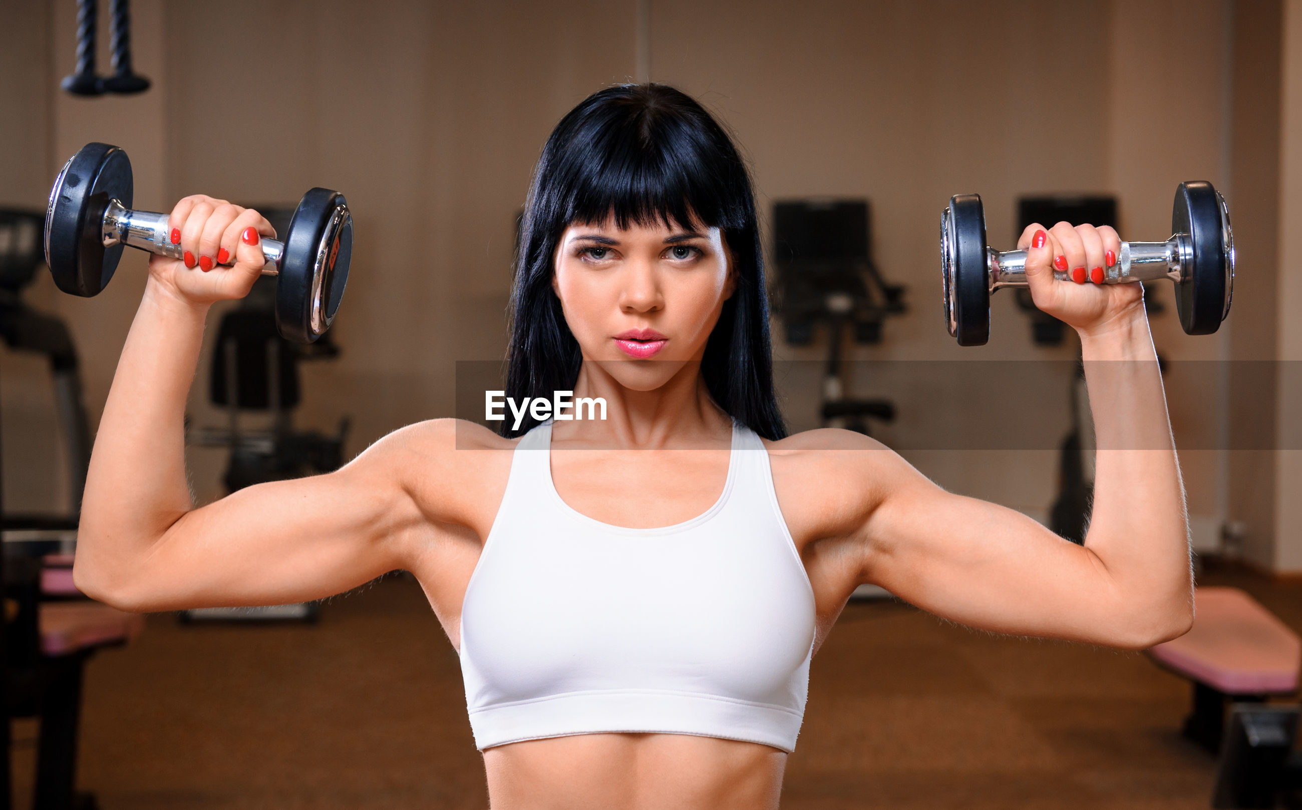 Beautiful young woman exercising in gym