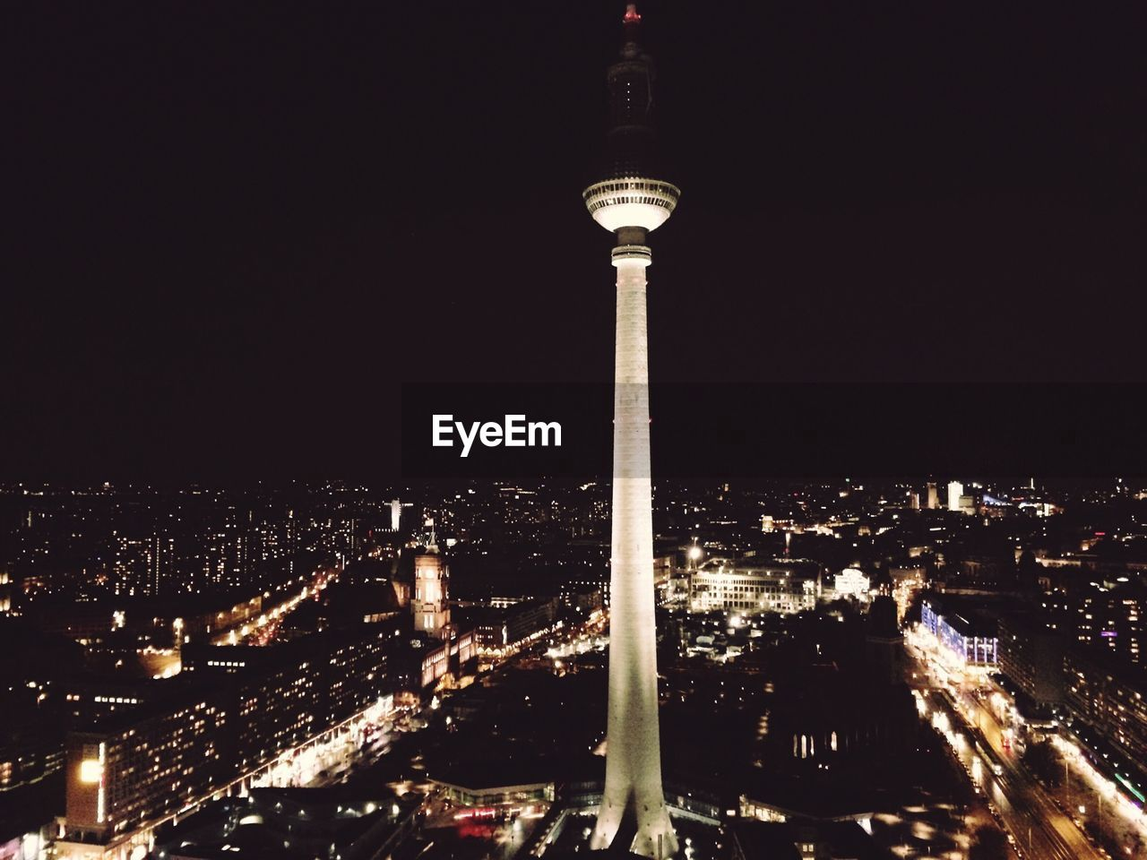 Fernsehturm tower amidst buildings against clear sky in city at night