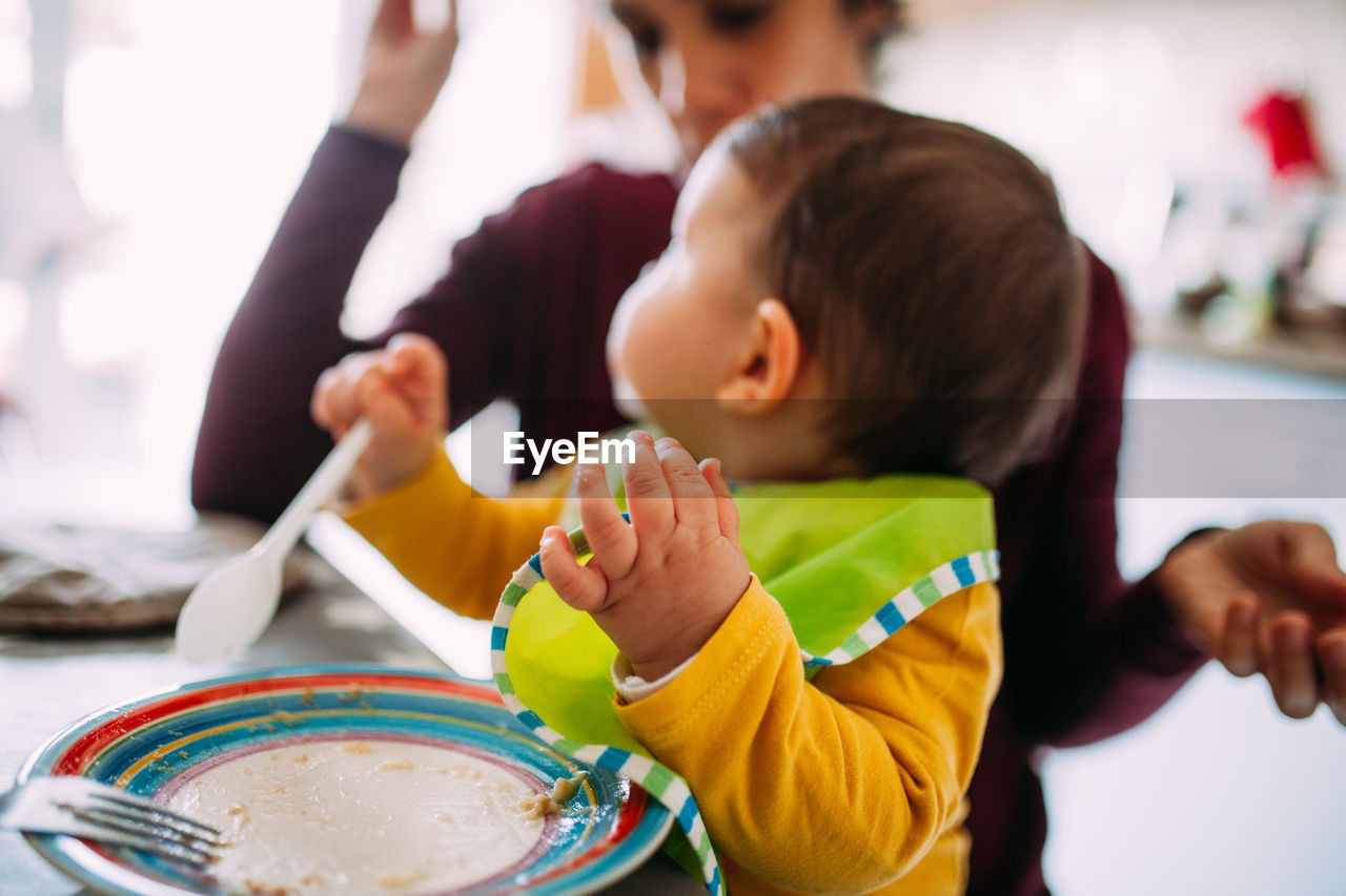 child, childhood, real people, girls, women, females, lifestyles, indoors, headshot, two people, boys, focus on foreground, males, food and drink, casual clothing, togetherness, sitting, innocence, people
