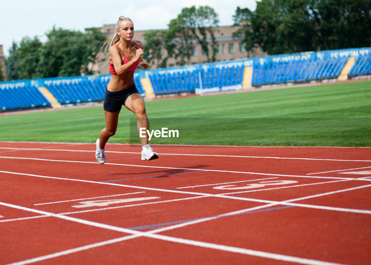 track and field, sport, running track, competition, one person, sports track, lifestyles, women, young adult, athlete, exercising, sports clothing, healthy lifestyle, full length, real people, day, determination, adult, effort