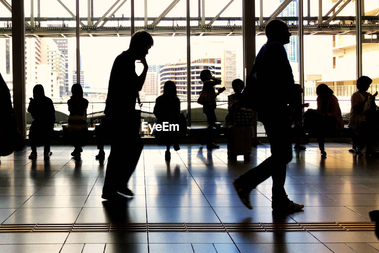 group of people, men, indoors, real people, flooring, silhouette, medium group of people, women, adult, group, day, people, lifestyles, airport, architecture, transportation, travel, walking, leisure activity, tiled floor, waiting