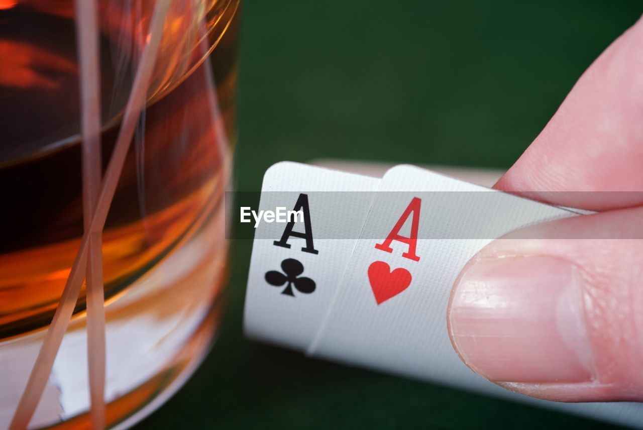 Cropped Image Of Hand Holding Cards By Drink On Table