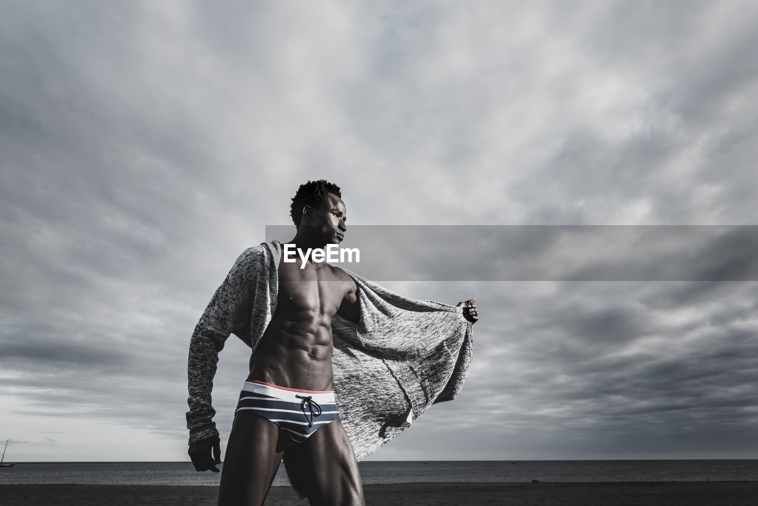 Low angle view of muscular man standing in underwear at beach against cloudy sky